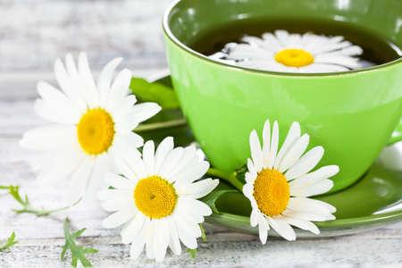 Närbild på en kopp med naturläkemedel kamomill te serveras i grönt keramik kopp och några vilda blommor på vitmålad träyta