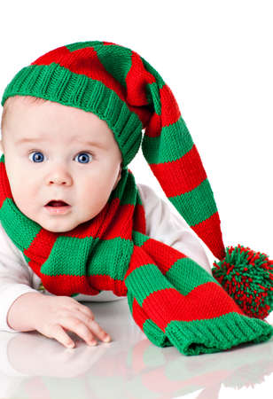 Closeup of cute little baby boy with blue eyes wearing striped Cristmas hat with pompon and scarf. More photos with same child in my portfolio photo