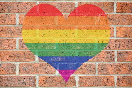pride: colored heart shape painted on old red brick wall