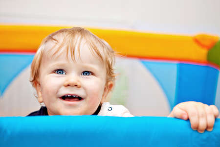yellow teeth: 11 months Baby boy reaching out of his bed holding the edge with hands and laughing.