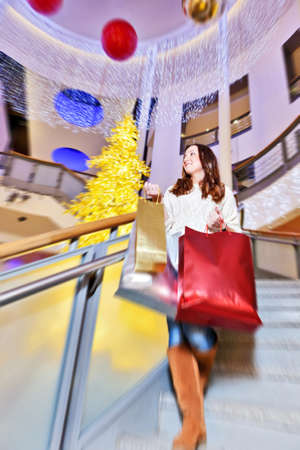 Beautiful young woman in white knitted sweater and blue jeans posing with shopping bags in mall during the Christmas sale. photo