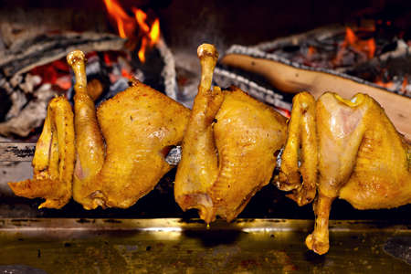 Free range chicken wings and thighs fire roasting traditional way on skewer  Stock Photo