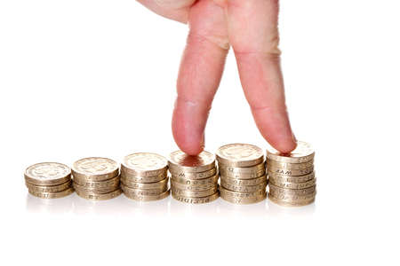 Fingers walking up on stacks of one pound coins on white background. Way to economical growth concept  photo