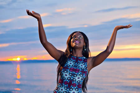 woman beach dress: Portrait of beautiful black African American woman posing with open hands up to the sky on the beach at sunset