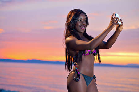 Portrait of beautiful black African American woman posing to take a selfie with her smartphone on the beach at sunset photo