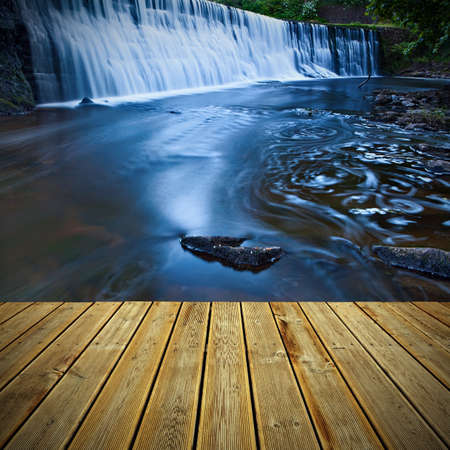 Striped wooden plank terrace with the view to waterfall on a river cliff photo