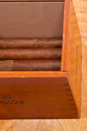 Genuine Cuban cigars and wooden varnished cigar box photo