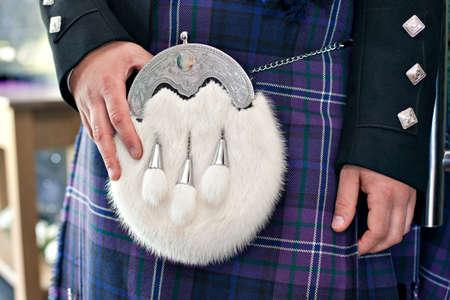 highlander: Primer plano de traje ceremonial masculina tradicional escocesa. El hombre de uniforme azul y falda escocesa de tartán con piel hermosa y sporran plata.