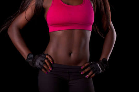 African female fit torso with exposed belly area on black background. Workout and healthy lifestyle result concept photo