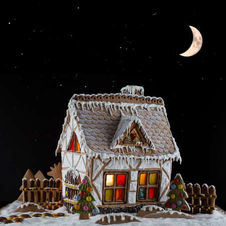 Decorative gingerbread house with lights inside on black background with moon and stars . Rural Christmas night scene
