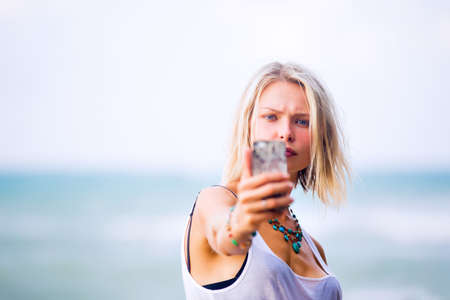 blonde blue eyes: Beautiful young blonde blue eyes woman taking a selfie on smart-phone outdoor at the rocky sea shore. Trendy fashion female model dressed in white top