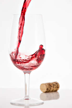 tannins: Pouring red wine into wineglass with splash on white background