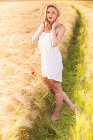 scottish female: Lonely beautiful young blonde Scottish girl in white dress with straw hat posing at golden wheat field expressing calmness emotions