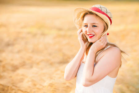 blonde blue eyes: Beautiful young blonde blue eyes Scottish girl in white dress with straw hat posing at golden wheat field expressing calmness emotions Stock Photo