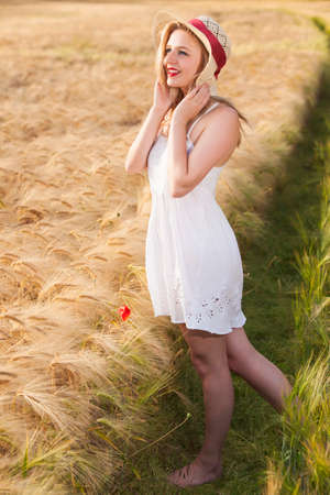 scottish female: Cheerful beautiful young blonde blue eyes Scottish girl in white dress with straw hat posing at golden wheat field expressing happyness Stock Photo
