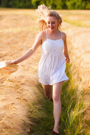 Happy young blonde Scottish girl in white dress with straw hat running through the golden wheat field photo