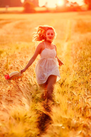 Happy young blonde Scottish girl in white dress with straw hat running through the golden wheat field on sunset light behind her photo