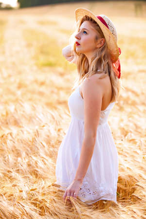blonde blue eyes: Lonely beautiful young blonde blue eyes Scottish girl in white dress with straw hat posing at golden wheat field expressing calmness emotions