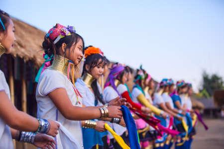 originate: CHIANG RAI, THAILAND - JANUARY 2015: Karen tribal girls dressed in traditional costumes  performing national dance near Mae Hong Son, Thailand, Chiang Rai. Padaung long neck hill tribe village, refugee community originate from neighboring Myanmar.