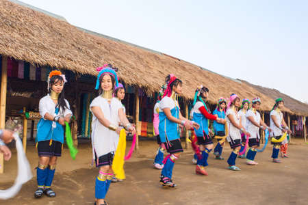 neighboring: CHIANG RAI, THAILAND - JANUARY 2015: Karen tribal girls dressed in traditional costumes  performing national dance near Mae Hong Son, Thailand, Chiang Rai. Padaung long neck hill tribe village, refugee community originate from neighboring Myanmar.