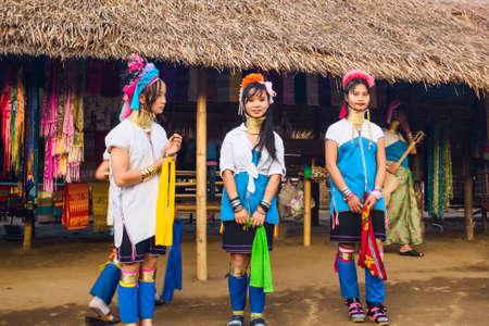 thai stretch: CHIANG RAI, THAILAND - JANUARY 2015: Karen tribal girls dressed in traditional costumes  performing national dance near Mae Hong Son, Thailand, Chiang Rai. Padaung long neck hill tribe village, refugee community originate from neighboring Myanmar.
