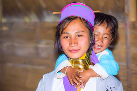 neighboring: CHIANG RAI, THAILAND - JANUARY 2015: Karen tribal woman with her child near Mae Hong Son, Thailand, Chiang Rai. Padaung long neck hill tribe village, refugee community originate from neighboring Myanmar. Editorial