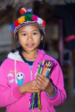 originate: CHIANG RAI, THAILAND - JANUARY 2015: Karen tribal girl selling souvenirs near Mae Hong Son, Thailand, Chiang Rai. Padaung long neck hill tribe village, refugee community originate from neighboring Myanmar.