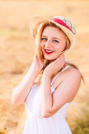 unconcerned: Lonely beautiful young blonde Scottish girl in white dress with straw hat posing at golden wheat field expressing calmness emotions