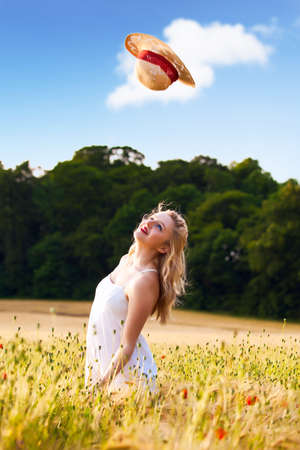 unconcerned: Lonely beautiful young blonde Scottish girl in white dress at golden wheat field catching her straw hat