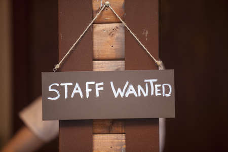 wooden post: Staff wanted inscription on a board hanging on wooden post. Stock Photo