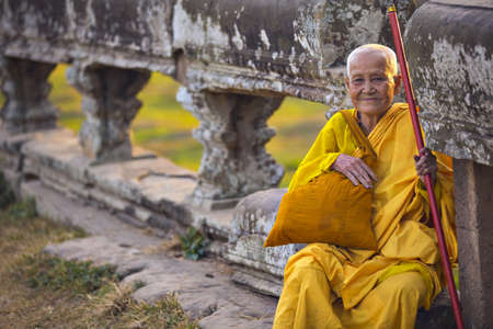 angkor wat: ANGKOR WAT, KRONG SIEM REAP, SIEM REAP, CAMBODIA-JANUARY 5, 2015: An unidentified old buddhist female monk dressed in orange toga at Angkor Wat temple.