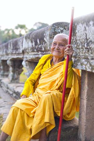 toga: Angkor Wat, Kr?ng SIEM REAP, SIEM REAP, CAMBOYA-5 DE ENERO DE 2015: Un viejo monje budista femenino no identificado vestido con toga naranja en templo de Angkor Wat.