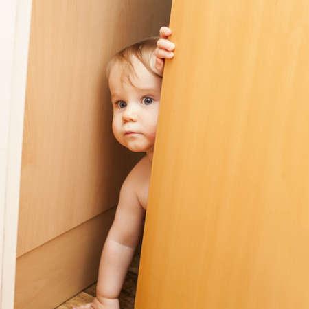 ajar: Curious cute baby toddler boy looking through ajar door