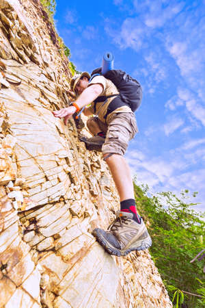 Close up of a man climbing up red rock dressed in hiking shoes, khaki color shorts and t-shirt with black rucksack.