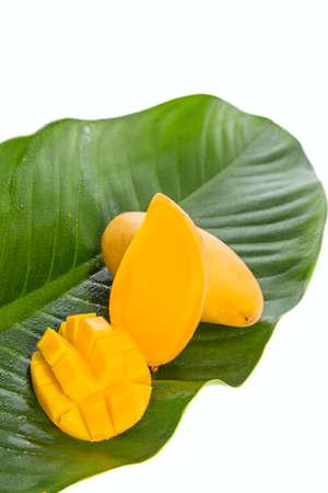 sweet segments: Yellow Mango fruit on banana leaf against white background