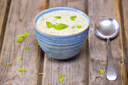 Bowl of broccoli and cheddar cheese soup served in blue crockery bowl on wooden table photo