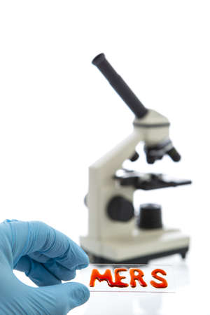 nhs: Hand in blue latex glove holds sample glass plate with blood inscripted MERS (aka novel coronavirus 2012 or Camel Flu) on it and microscope on white background