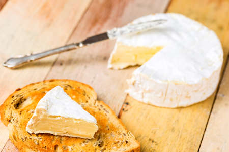 wedge: Camembert cheese with cut wedge on toasted bread slice and vintage knife on wooden table