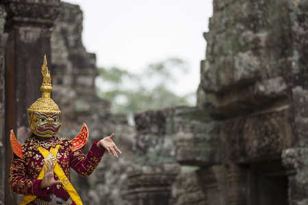 godhead: Hindu cultural legend of deity with hands gestures reenacting by an actor in colorful costume at Bayon temple ruins, Angkor Wat, Siem Reap
