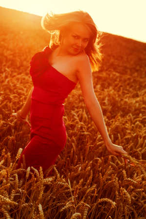 unconcerned: Young girl in dress walking at wheat field