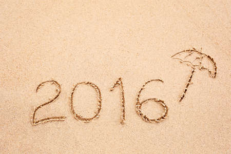 umbella: Inscription of the year 2016 written in the wet yellow beach sand. Concept of celebrating the New Year at some exotic place