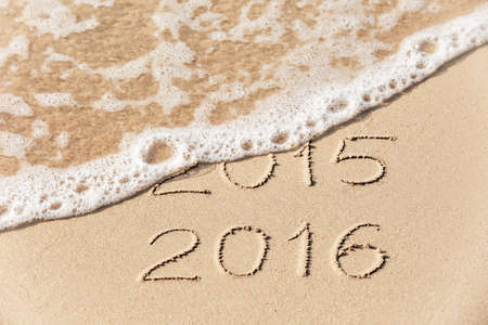 2015 2016 inscription written in the wet yellow beach sand being washed with sea water wave. Concept of celebrating the New Year at some exotic place