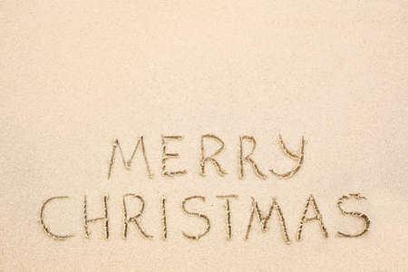 Merry Christmas inscription on wet yellow shoreline beach sand. Holiday wish message