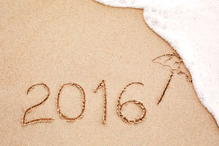 umbella: Foaming sea wave coming to wash inscription of the year 2016 written in the wet yellow beach sand. Concept of celebrating the New Year at some exotic place