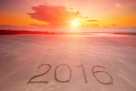 2016 inskrift skriven i den våta gula sandstranden. Begreppet fira det nya året.