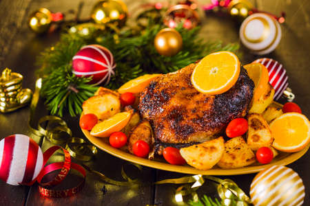 potato: Christmas roast duck served with potatoes, orange and tomatoes on wooden festive decorated table Stock Photo