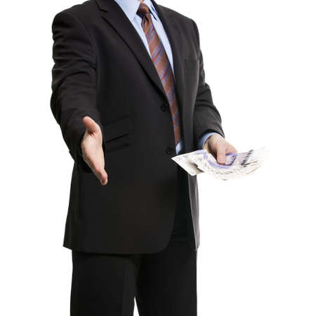 stockbroker: Some unrecognizable Businessman in dark suit shows a Spread of 20 British Pounds Sterling banknotes and offers a handshake, symbolizing Success, Business offer, Deal. Isolated on white background.