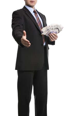 salarios: Algunos empresario irreconocible en traje oscuro muestra un diferencial de 20 libras esterlinas billetes de banco Sterling y ofrece un apretón de manos, que simboliza el éxito, la oferta de negocios, Deal. Aislado en el fondo blanco.