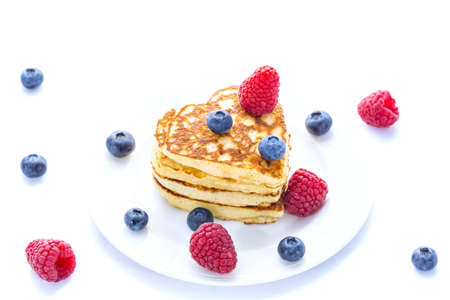 Pile of heart shaped pancakes with blueberries and raspberries on white background Stock Photo