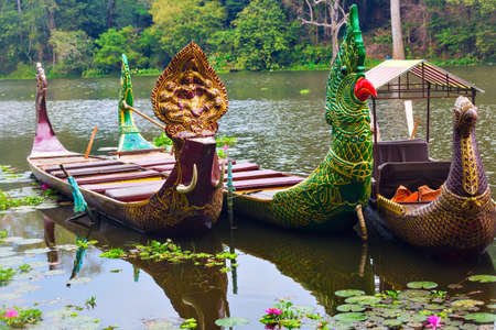 shiva: Traditional khmer boats with green parrot and a bird heads and Shiva deity carved bows at Bayon moat pier waiting for tourists
